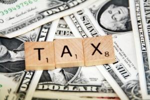 Scrabble tile spelling Taxes plus money